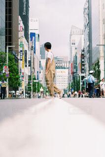 高層ビルの隣の通りを歩く人々のグループの写真・画像素材[2440463]
