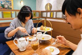 食べ物の皿を持ってテーブルに座っている女性の写真・画像素材[2440469]