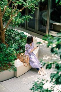 庭のベンチに座っている人の写真・画像素材[2440494]
