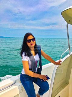 水の体の横にボートに立っている女性 - No.963125