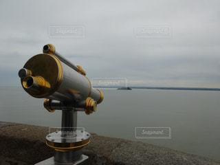 望遠鏡のクローズアップと小さな島の写真・画像素材[2499983]