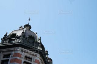 建物の側に時計と大きな背の高い塔の写真・画像素材[969610]