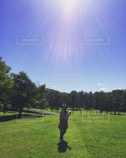 草の覆われてフィールド上に立っている人の写真・画像素材[1036946]
