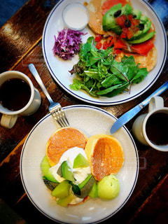 テーブルの上の皿の上に食べ物のボウルの写真・画像素材[976395]