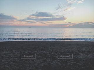 水の体の近くのビーチに立っている人 - No.970488