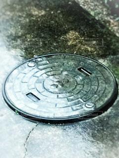 雨の日のマンホールの写真・画像素材[1179827]