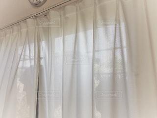カーテン越しの洗濯物の写真・画像素材[1196873]