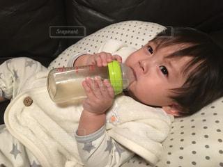 哺乳瓶でジュースを飲むゆうきボーイの写真・画像素材[977737]