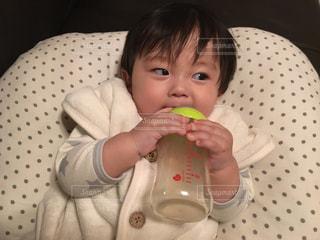 哺乳瓶でジュースを飲むゆうきボーイの写真・画像素材[977739]