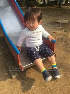 滑り台に座っている小さな子供ゆうきボーイ。の写真・画像素材[2211396]