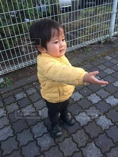 フェンスの前に歩道に立つ泣き顔の小さな子供ゆうきボーイ。の写真・画像素材[2211406]