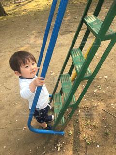 公園の滑り台の階段を登ろうとする小さな子供ゆうきボーイ。の写真・画像素材[2223831]