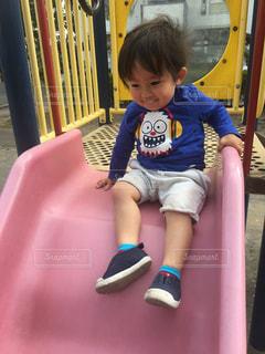 滑り台に座っている小さな子供ゆうきボーイ。の写真・画像素材[2228979]