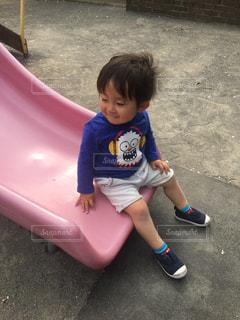 滑り台に座っている小さな子供ゆうきボーイ。の写真・画像素材[2228980]