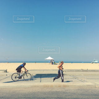 ビーチでバイクに乗っている人とランニングしてる人の写真・画像素材[971135]