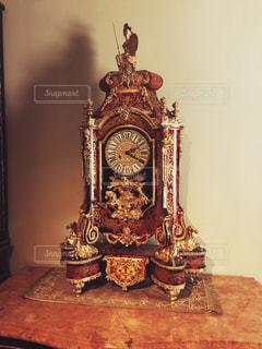 テーブルの上の金の時計の写真・画像素材[1012763]