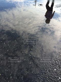水たまりに映る空と子供の写真・画像素材[974744]