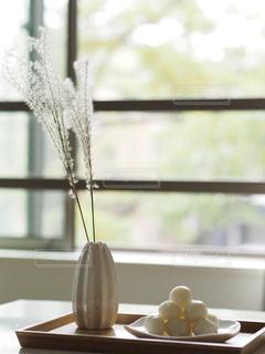 ウィンドウの横にあるテーブルの上の花の花瓶の写真・画像素材[976570]