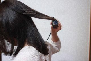 ヘアアイロンで髪を巻く女性の写真・画像素材[1175983]