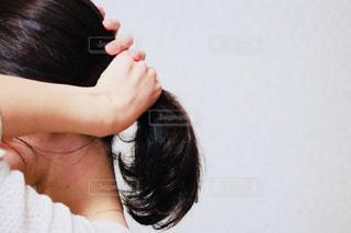 髪を結ぶ女性の写真・画像素材[1176001]