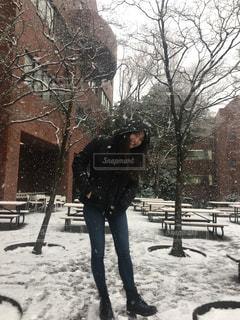 雪に覆われた歩道を歩く女性の写真・画像素材[975370]