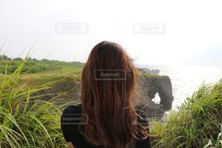 水の体の前で立っている女性の写真・画像素材[975371]