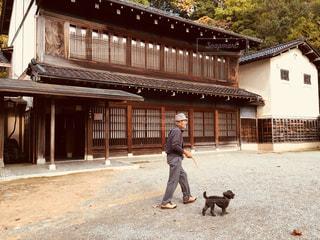 男と犬は建物の前に歩いています。の写真・画像素材[975646]