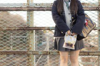 橋の上で誰かを待っている高校生。の写真・画像素材[1005771]