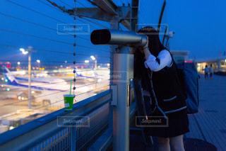 空港の展望デッキで飛行機を双眼鏡で見ている飛行機マニアのJKの写真・画像素材[1160127]