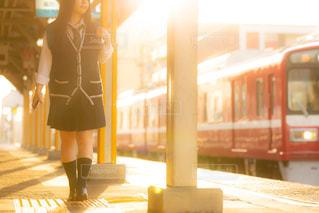 夕日が差し込む駅のホームを歩くJKの写真・画像素材[1160129]