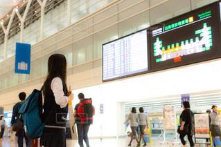 空港の出発ロビーで搭乗案内を見つめる女子高生(JK)の写真・画像素材[1160130]