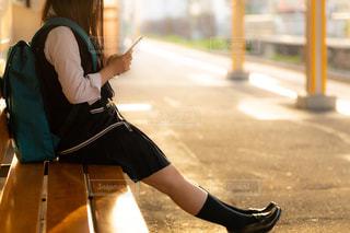 夕日が差し込むホームのベンチに座って電車を待つJKの写真・画像素材[1160133]