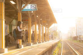 夕日が差し込む駅のホームで電車を待つ帰り道のJKの写真・画像素材[1160134]