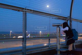 空港の展望デッキで飛行機を双眼鏡で見ているJKの写真・画像素材[1160168]