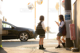 西日が差し込むバス停でバスを待つJKの写真・画像素材[1168908]