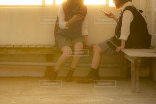 バス停のベンチに座るJK2人の写真・画像素材[1168921]
