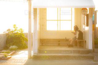夕方の西日が差し込むバス停のベンチに座って談笑するJKの写真・画像素材[1168922]