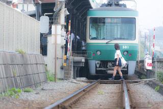 踏切を渡る女子高生の写真・画像素材[1209224]