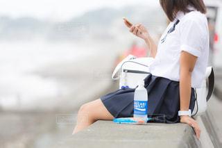 海の見える堤防に座るJKの写真・画像素材[1209236]