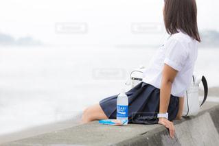 堤防に座り海を眺めるJKの写真・画像素材[1209237]