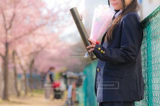 卒業証書の入った筒を見つめて、物思いに耽る女子高生の写真・画像素材[1777710]