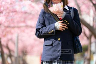 桜並木の道で、ブーケを持って歩く高校生の写真・画像素材[1837047]