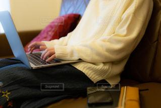ソファに座ってパソコンで作業をする女性の写真・画像素材[2009798]