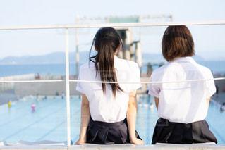 プールの見える観客席に座る女子高生の写真・画像素材[3167977]