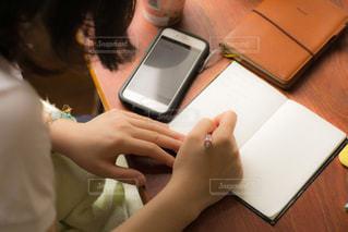 イスに座り机でノートを書いている高校生の写真・画像素材[3170408]