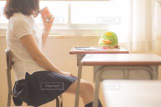 イスに座りドリンクを飲む女子高生の写真・画像素材[3170410]