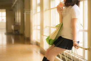 廊下の柵に腰かけてドリンクを飲む女子高生の写真・画像素材[3170412]