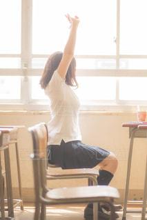 イスに座りノビをしている女子高生の写真・画像素材[3170409]