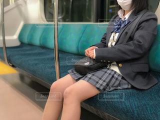 電車のイスに座るマスク姿の女子高生の写真・画像素材[3217381]