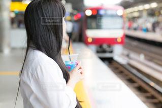 ホームで冷たい飲みものを飲みながら、電車を待っている女子高生の写真・画像素材[3293955]
